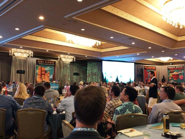 話に出ているグローバルな経営会議の様子。この会場に360度を写すカメラが入っている。ハワイで開催され、出席者は皆、アロハシャツにハーフパンツといったカジュアルな服装。写真の右側で、マイクを手に、歩きながら話しているのが小出さん